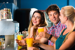People in club or bar drinking. Young people in club or bar drinking cocktails and having fun Royalty Free Stock Photos