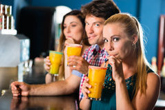 People in club or bar drinking. Young people in club or bar drinking cocktails and having fun Royalty Free Stock Images