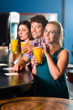 People in club or bar drinking. Young people in club or bar drinking cocktails and having fun Stock Images
