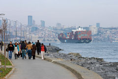 People on the coast and large ship on Bosphorus Royalty Free Stock Photo