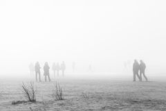 People in coats walking along the foggy beach Stock Image