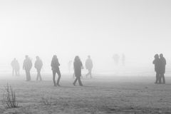 People in coats walking along the foggy beach Royalty Free Stock Images