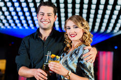 People with cocktails in bar or club Stock Images