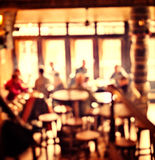 People in Coffee shop blur background with bokeh lights Royalty Free Stock Images