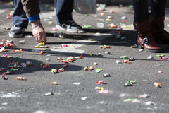 People collecting caramels from asphalt Royalty Free Stock Image