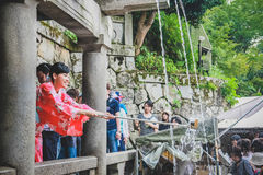 People collecting water from the Otowa-no-taki waterfall at Kiyomizu temple Royalty Free Stock Photography
