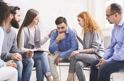 People comforting depressed addict man at rehab group meeting royalty free stock images