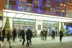 People coming in and out from the large decorated shopping center Palladium in Prague on the Republic square. PRAGUE, CZECH REPUBLIC - DECEMBER, 13, 2017 Stock Photography