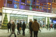 People coming in and out from the large decorated shopping center Palladium in Prague on the Republic square. PRAGUE, CZECH REPUBLIC - DECEMBER, 13, 2017 Stock Image