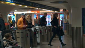 People coming through the subway wicket. STOCKHOLM, SWEDEN - APRIL 26, 2015: Slow motion clip of people using transport card to get through the ticket gate in stock video footage