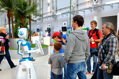 People communicate with the robot. SOCHI, RUSSIA - November 21, 2014: People communicate with the robot in Sochi. Here there was the World Robotic Olympiad 2014 Royalty Free Stock Photography