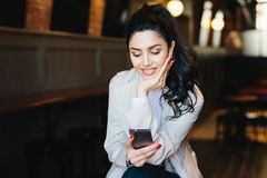 People, communication and lifestyle concept. Happy brunette woman with attractive face looking elegantly making video call, using royalty free stock photos