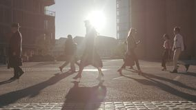 People commuting to office early in the morning. Men and woman commuting to office early in the morning with bright sunlight around. Business people walking on a stock video