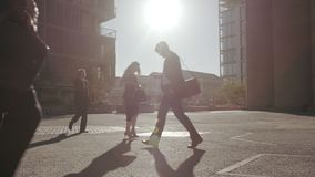 People commuting to office on a sunny morning. Business Men and women walking on city street with bright sunlight stock footage
