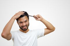 people concept - smiling young man brushing hair with comb on white background stock image