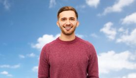 Smiling young man over blue sky background royalty free stock photo