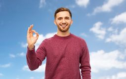 Smiling man showing ok hand sign over blue sky royalty free stock photography