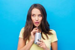 Young woman or teenage girl drinking soda from can stock photo