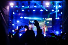 People at concert shooting video or photo stock images