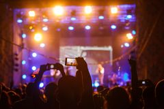 People at concert shooting video or photo stock image