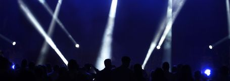 People at the concert and reflectors. Dark blue stage lights crisscrossed the stage spotlights and black shadows of people royalty free stock images