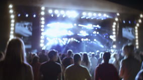People on a concert. Summer music festival, people listening to the concert. Heaving crowd. Night stock footage