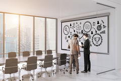 People in conference room with victory poser. Rear view of two businessmen in a white office of a company with a large table, a panoramic window and a victory Stock Photography