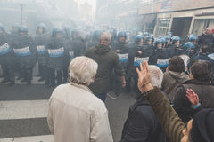 People confronting riot police in Milan, Italy. MILAN, ITALY - NOVEMBER 13: People confront riot police during a march in the city streets to protest agaist the Royalty Free Stock Image