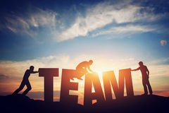 People connect letters to compose the team word. Teamwork concept. Idea. Sunset positive light Stock Photo