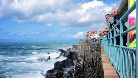 People contemplate stormy sea Passeggiata Anita Garibaldi trail Genova Italy. People contemplate the stormy sea from the blue railing of the Passeggiata Anita stock footage