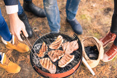 People cooking meat on charcoal grill Royalty Free Stock Images