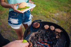 People cooking meet on barbeque grill and making hamburger outdoors Royalty Free Stock Images