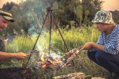 People cooking outdoors barbecue on fire in summer camp Royalty Free Stock Photos