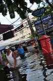 People are coping with the water in a flooded street of Bangkok, Thailand in October 2011.  Royalty Free Stock Images