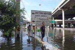 People are coping with the water in a flooded street in Rangsit, Thailand, in October 2011.  Stock Photos