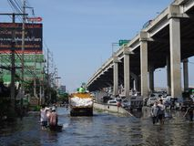 People are coping with the water in a flooded street in Rangsit, Thailand, in October 2011.  Stock Photography