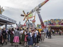 People in costume at the Oktoberfest. People in costume in front of the attractions and amusement rides of the Oktoberfest, Munich, Germany royalty free stock photos