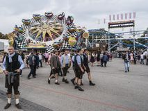 People in costume at the Oktoberfest. People in costume in front of the attractions and amusement rides of the Oktoberfest, Munich, Germany stock photo