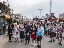 People in costume at the Oktoberfest. People in costume in front of the attractions and amusement rides of the Oktoberfest, Munich, Germany stock images