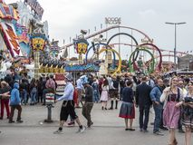 People in costume at the Oktoberfest. People in costume in front of the attractions and amusement rides of the Oktoberfest, Munich, Germany royalty free stock image