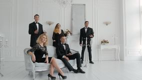 People in costumes and dresses sings. Group of people in costumes and dresses sings against the backdrop of a bright and spacious room in a luxury style. Three stock video