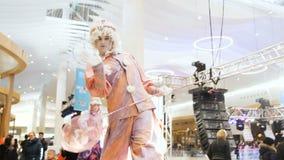 People in costumes on stilts entertain passersby. Kazan, Tatarstan/Russia - March 14 2018: closeup talented people in bright carnival costumes on stilts stock video footage