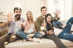 People on couch throwing popcorn upside Stock Photos
