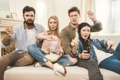 People on couch throwing popcorn upside Royalty Free Stock Photography