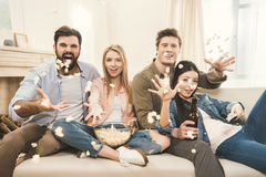 People on couch throwing popcorn upside Royalty Free Stock Images