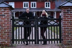 People: Couple in front of their house. Couple posing in front of an old house Royalty Free Stock Image