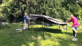 People cover metal arbour structure with canvas soft cloth stock video