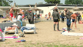 People covered with therapeutic mud at Techirghiol. Picture taken at Techirghiol lake.nnTechirghiol is a lake in Northern Dobrogea, Romania, near the town with Stock Images