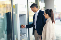 People with credit card standing next to the ATM to withdraw money. Young people with credit card standing next to the ATM to withdraw money Royalty Free Stock Images