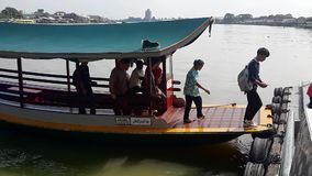 People cross Chao Phraya River on a small boat. Pakkret, Nonthaburi, Thailand - April 19, 2018: People cross Chao Phraya River on a small boat on April 19, 2018 stock footage